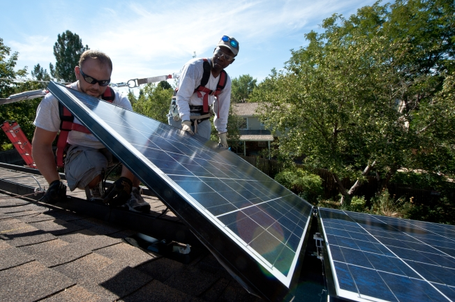 Workers installing solar on a roof. Photo credit: Dennis Schroeder, NREL