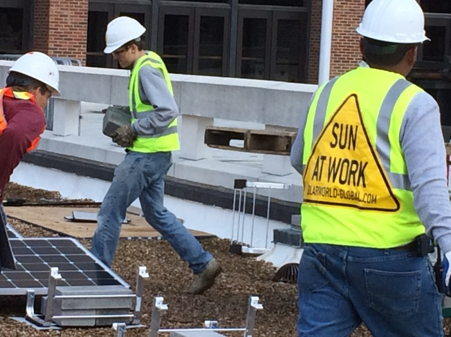 Workers install solar panels at the University of Richmond.