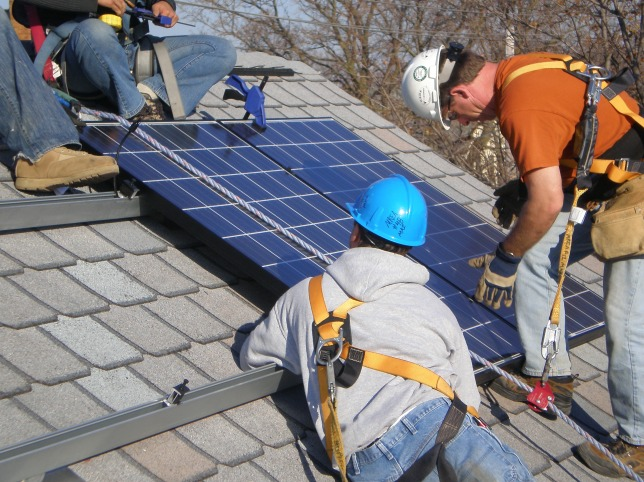 workers installing solar panels on a roof