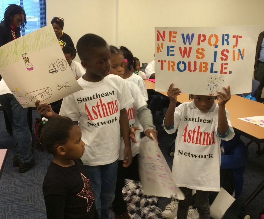 "children holding signs, wearing T-shirts that read ""Southeast asthma network"""