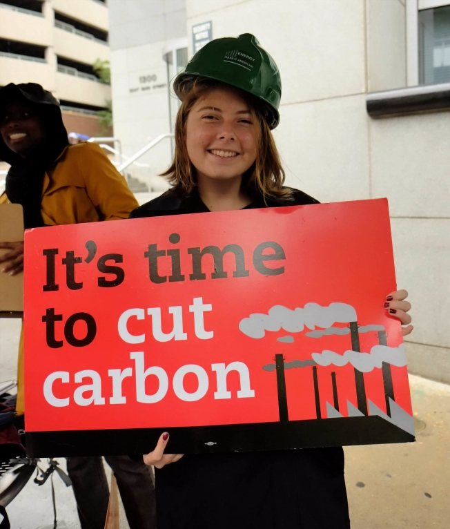 woman holding sign reading It's time to cut carbon