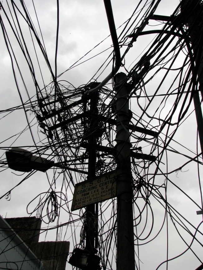 Tangled electric distribution wires illustrate the problems caused by poor grid planning