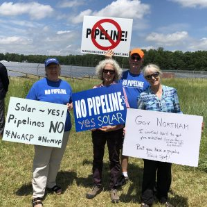 gas pipeline protesters standing in front of solar panels