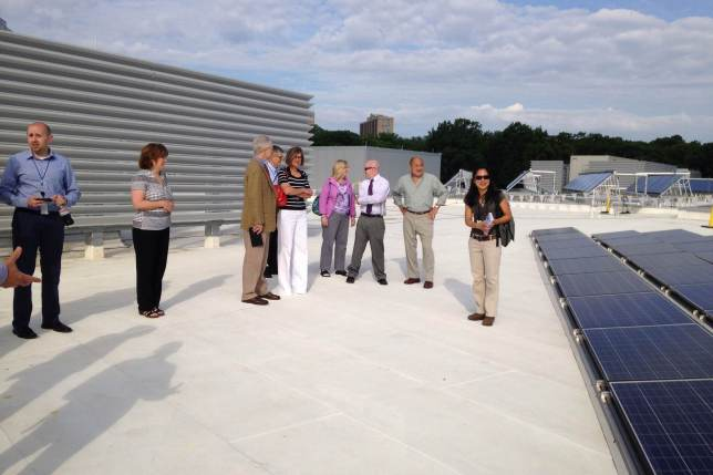 people standing by solar panels on a high school.