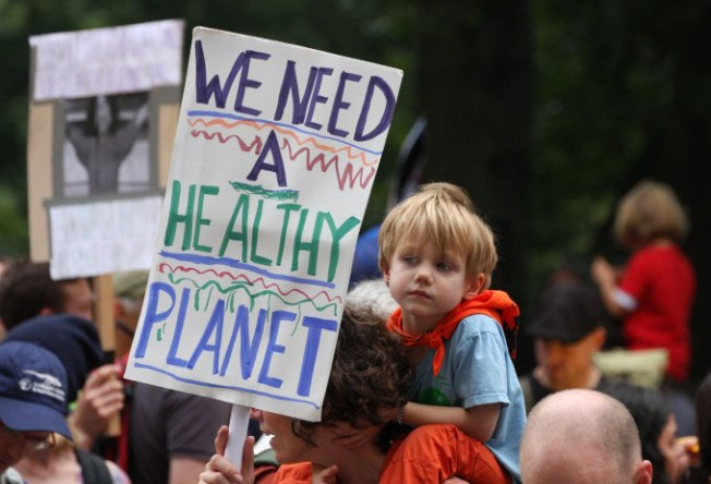 "Child on father's shoulders with sign reading ""We need a healthy planet"""
