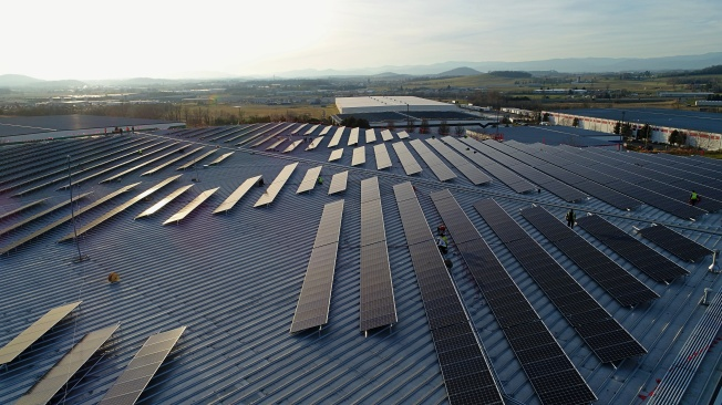 workers complete a rooftop solar array on a warehouse
