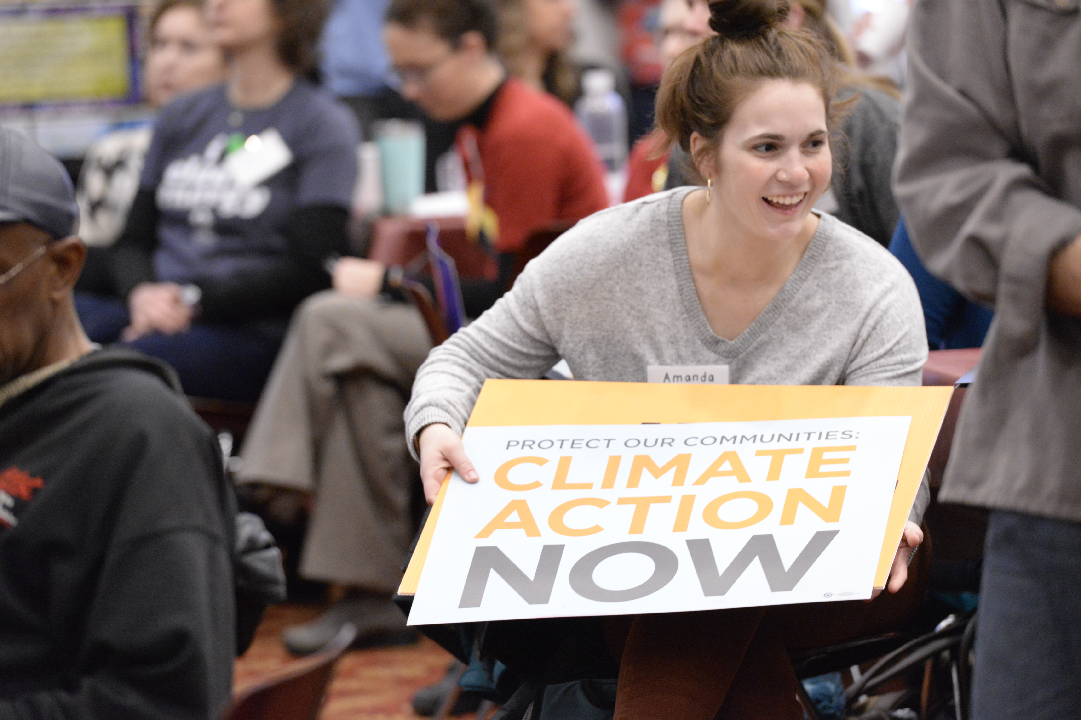 Young woman holding sign that says Climate Action Now