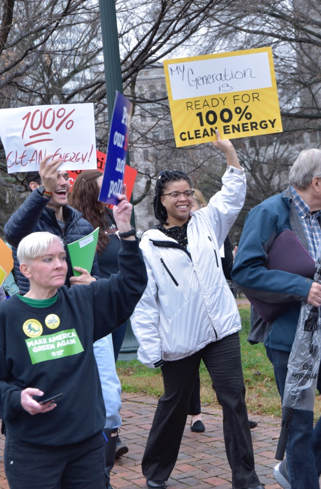 advocates holding clean energy signs